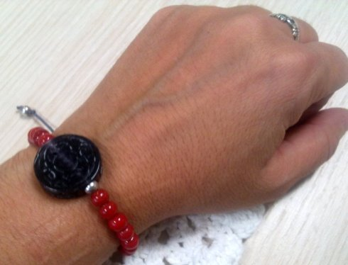 black carved stone and red beads